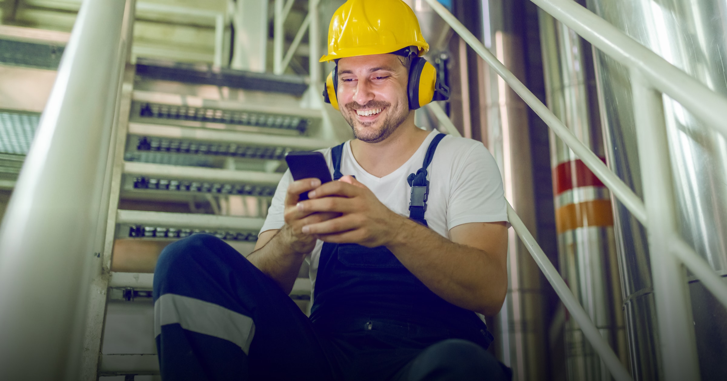 Frontline worker in factory uses employee app to connect and engage with coworkers